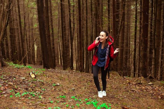Felice bella giovane donna bruna con uno smartphone sta camminando in cima alla montagna durante le escursioni