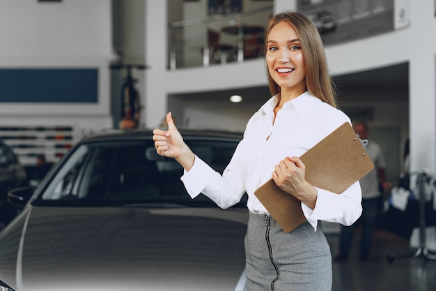 Felice bella giovane donna concessionario auto in showroom si chiuda