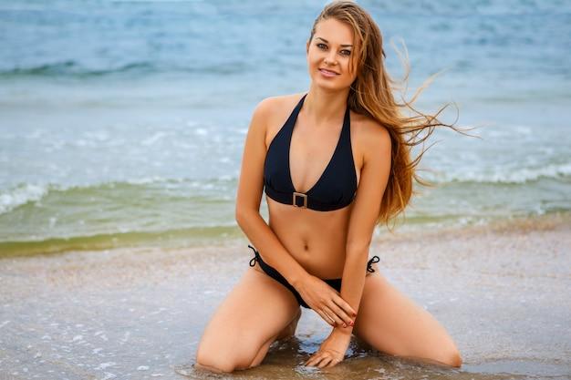 Felice bella ragazza sulla spiaggia in costume da bagno