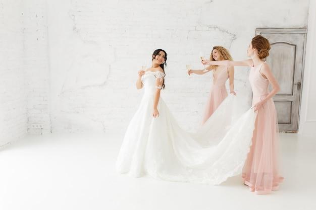 Felice bella sposa e damigella d'onore regolando il suo abito da sposa. bere champagne.