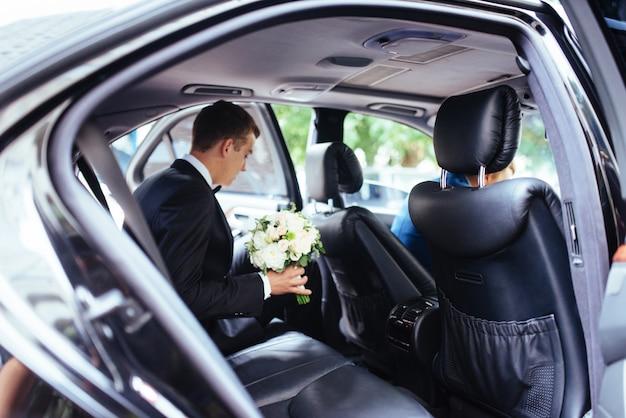 Felice bella sposa, seduto in macchina di nozze con un mazzo di fiori