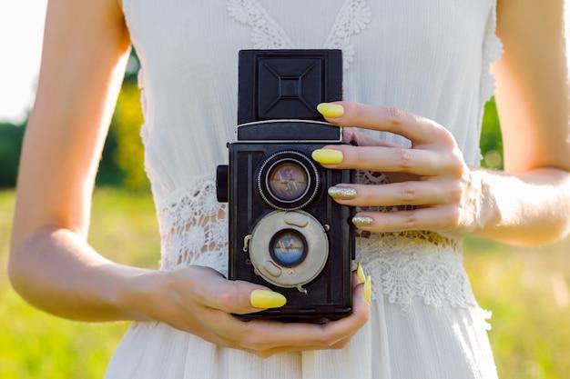Felice bello divertimento ragazza donna hipster indossare abito lungo bianco tenere foto vecchio antico raro retrò film macchina fotografica con due obiettivi su grande grande ampia estate calda primavera soleggiata campo di luce verde