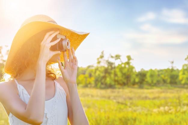 Felice bello divertimento ragazza donna pantaloni a vita bassa indossare cappello di paglia abito bianco lungo tenere stretta scattare foto antica antica macchina fotografica rara sulla grande grande ampia estate calda primavera soleggiata campo di luce verde tra alberi da frutta