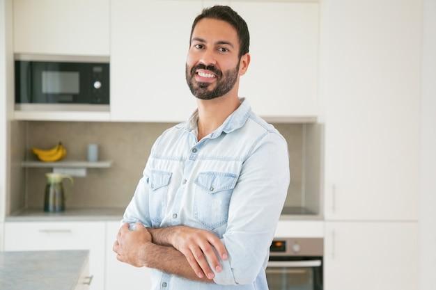 Felice bello uomo latino dai capelli scuri in posa con le braccia conserte in cucina