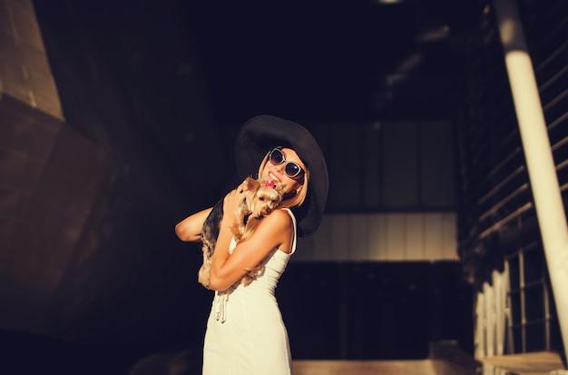Felice bionda in elegante cappello con cane