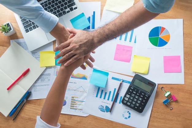 Felice business team dando alta in ufficio affari unire la mano