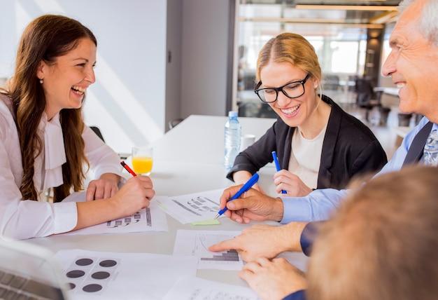 Felice businesspeople discutendo un piano finanziario nella riunione