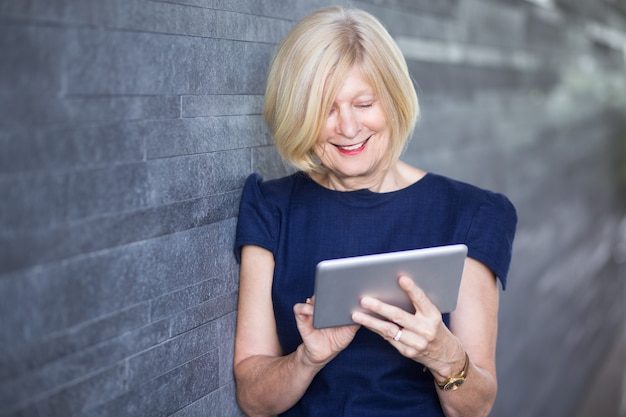Felice businesswoman senior utilizzando tablet digitale
