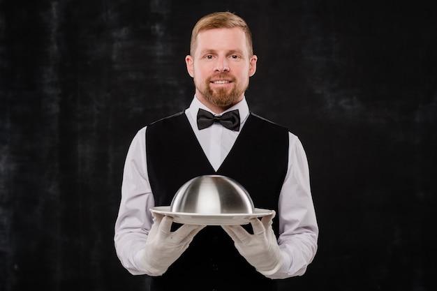 Felice cameriere elegante del ristorante di classe in panciotto nero e papillon e camicia bianca e guanti che tengono cloche