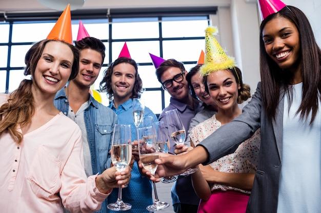 Felice collega bere champagne per festeggiare un compleanno