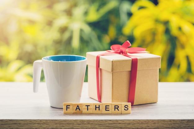 Felice concetto di giorno di fathre tazza di caffè e regalo sul tavolo di legno con la luce del sole.