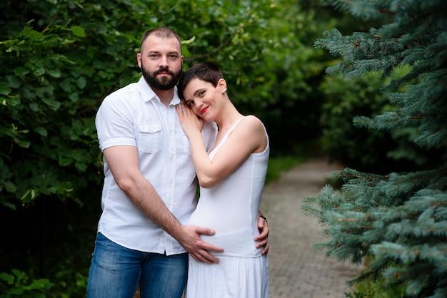 Felice coppia incinta all'aperto.