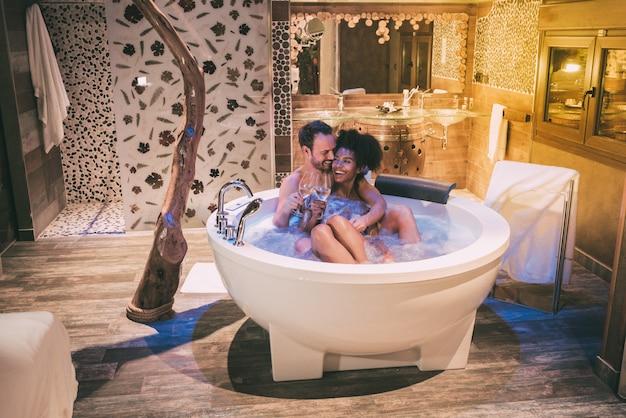Felice coppia interrazziale rilassata nella vasca idromassaggio godendosi e bevendo vino