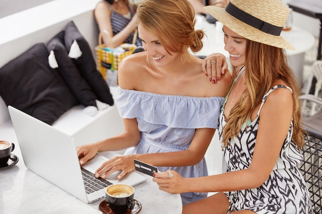 Felice coppia lesbica omosessuale femminile gode di wifi gratuito e divertirsi insieme al bar, utilizzare un computer portatile generico, controllare o verificare il conto, fare acquisti online, utilizzare servizi bancari per l'acquisto