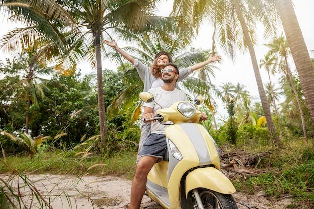 Felice coppia multinazionale che viaggiano su una moto nella giungla, luna di miele, vacanze,