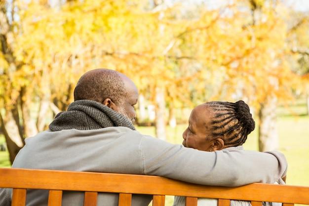 Felice coppia senior discutendo insieme su una panchina