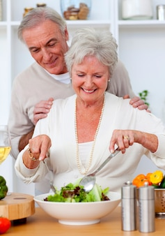 Felice coppia senior eeating un'insalata in cucina