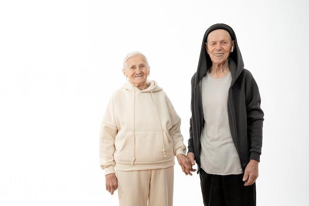 Felice coppia senior elegante in abiti casual con airpods bianchi nelle orecchie