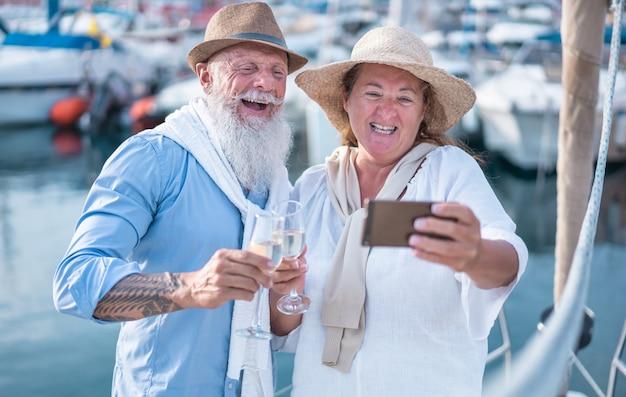 Felice coppia senior facendo selfie, tifo con champagne su una barca a vela durante la vacanza anniversario