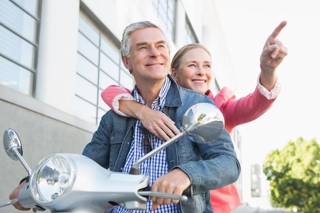Felice coppia senior in sella a un ciclomotore