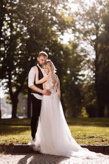 Felice coppia sposata in abiti da sposa semplici. sposi coppia di sposi alla moda. elegante abito bianco sulla sposa. concetto di matrimonio.