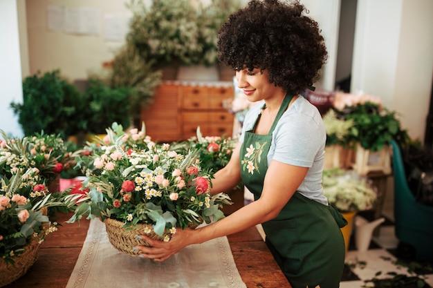 Felice donna africana che organizza cesto di fiori sulla scrivania