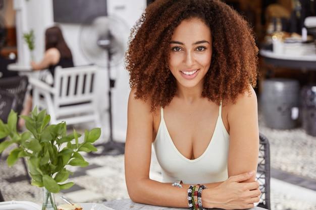 Felice donna afroamericana con espressione positiva, indossa abiti casual, ha una folta acconciatura afro, si siede contro un'accogliente caffetteria, trascorre le pause di lavoro da sola, andando a bere. espressioni facciali