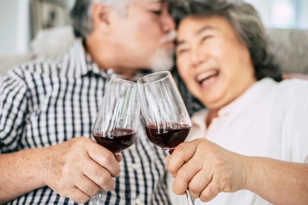 Felice donna anziana e suo marito bere vino e felicità