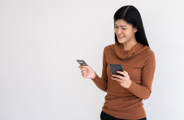 Felice donna asiatica in possesso di carta di credito e smartphone per il mobile banking su internet.