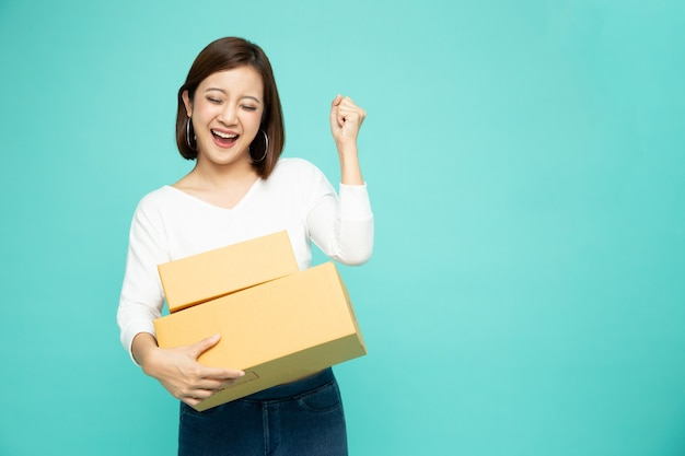 Felice donna asiatica tenendo il pacchetto cassetta dei pacchi