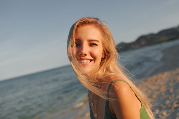 Felice donna bionda con un sorriso perfetto divertirsi sulla spiaggia assolata, guardando la fotocamera, correre e ballare