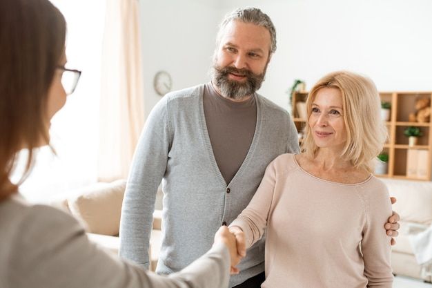Felice donna bionda matura e suo marito in abbigliamento casual che accolgono il loro agente immobiliare a casa