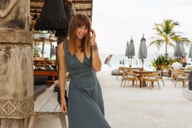 Felice donna bruna in abito sexy in posa in un elegante ristorante sulla spiaggia in stile asiatico.