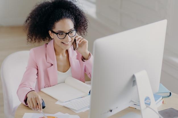 Felice donna dai capelli ricci indossa occhiali da vista, giacca rosa, guarda attentamente il display del computer