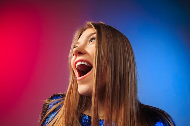 Felice donna in piedi, sorridente su studio colorato.