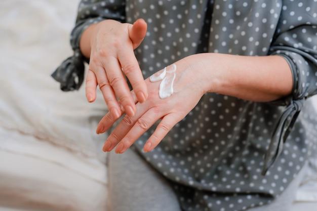 Felice donna matura in buona salute applica una crema cosmetica idratante antietà alle sue mani, sorride a una donna di mezza età con una cura della pelle morbida e pulita e bellezza