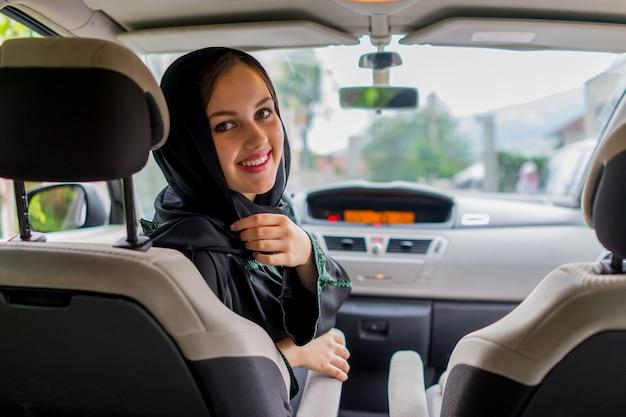 Felice donna musulmana e suo figlio alla guida di un'auto