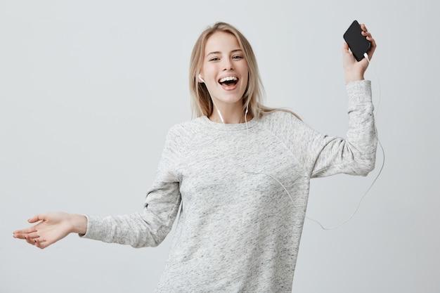 Felice donna positiva balla di gioia, tiene il cellulare, sorride ampiamente, ascolta le canzoni preferite con gli auricolari bianchi, usa la musica ap