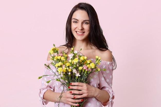 Felice donna positiva con i capelli scuri, tiene i fiori in mano, sorride positivamente, gode di una calda giornata primaverile, vestita in elegante abito a pois