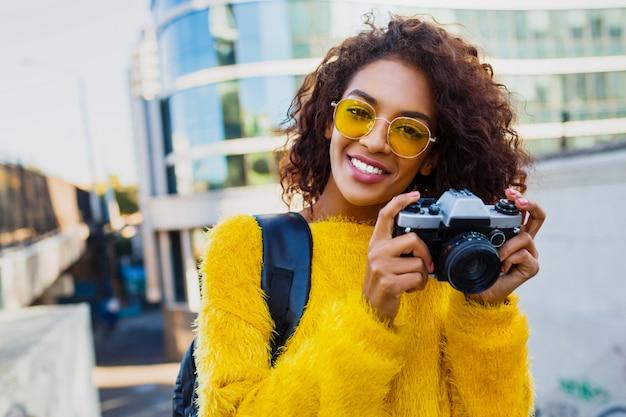 Felice donna sicura di sé tenendo la macchina fotografica e camminare nella grande città moderna. w