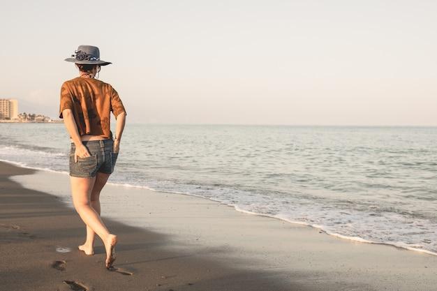 Felice donna spensierata godendo il bellissimo tramonto sulla spiaggia