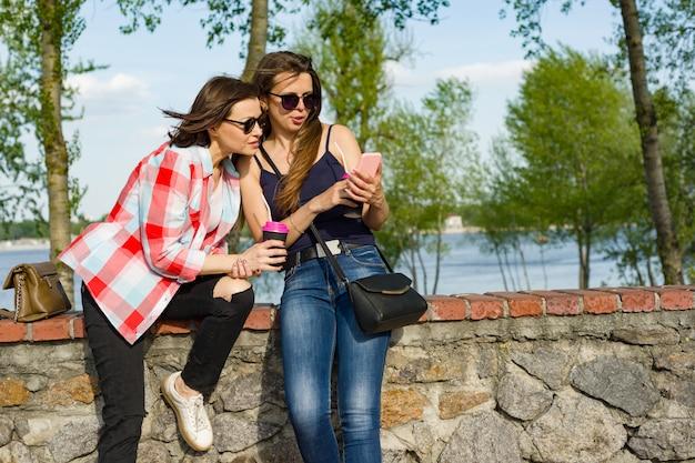 Felice due amiche con lo smartphone