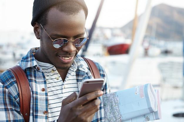 Felice e allegro uomo afroamericano che viaggia da solo in una località turistica europea con la mappa cartacea, guardando eccitato alla ricerca di ristoranti o ostelli nelle vicinanze usando il suo smartphone, vestito casualmente
