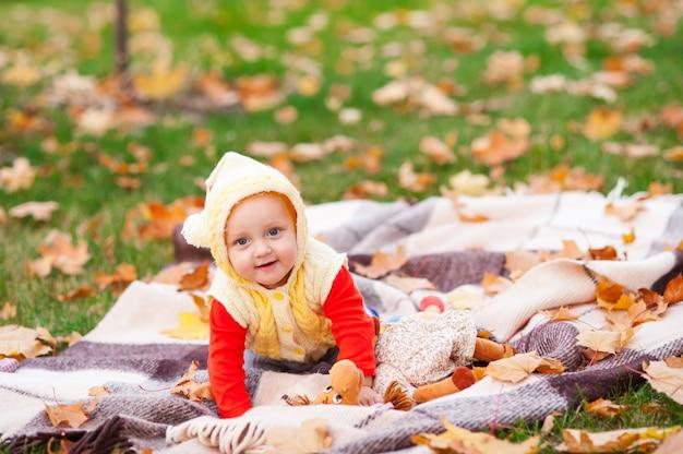 Felice e bambina sta giocando nel parco d'autunno.