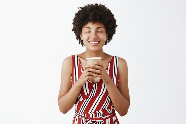 Felice e carina giovane donna afroamericana con acconciatura riccia, tenendo il bicchiere di carta con entrambe le mani, chiudendo gli occhi e sorridendo dalla soddisfazione
