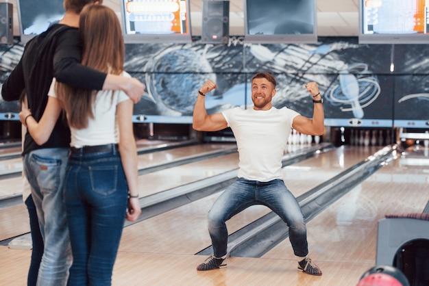 Felice e mostrando i muscoli. i giovani amici allegri si divertono al bowling durante i fine settimana