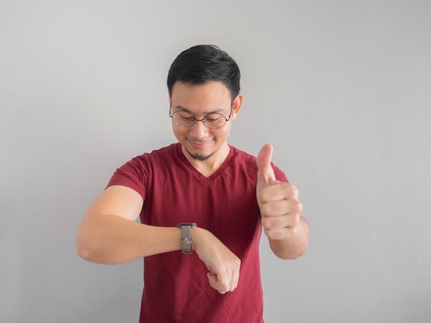 Felice e sorpreso uomo asiatico che sta guardando il suo orologio.
