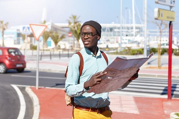 Felice eccitato turista dalla pelle scura, vestito con abiti eleganti, camminando per la metropoli con la mappa di carta nelle sue mani viaggiatore nero in piedi sulla strada, tenendo la guida della città, trascorrendo le vacanze all'estero