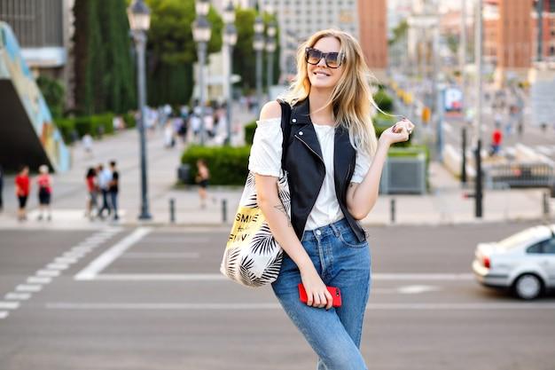 Felice elegante donna bionda in posa per strada, indossa jeans e gilet in pelle, viaggio atmosfera turistica, tempo soleggiato primavera estate