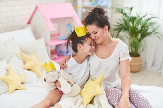 Felice famiglia amorevole. ãƒâ'â'âœãƒâƒã'â'â'ã'â¾ãƒâƒã'âââ e la figlia gioca in corone e si coccola sul letto.